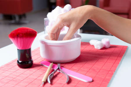hand dipped in a white bowl ready to a manicure treatment on a placemat on a table, near a nail file, a brush and a cuticule remover at a beauty salon
