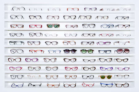 exhibitor of glasses consisting of shelves of fashionable glasses shown on a wall at the optical shop Stok Fotoğraf