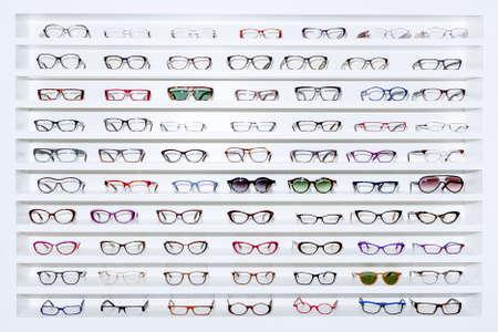 Wystawca okulary składające się z półek modnych okularach pokazano na ścianie w sklepie optycznym Zdjęcie Seryjne