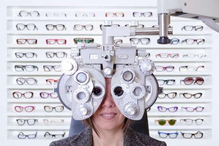 expositor: primer plano de medici�n de la vista de una mujer joven con un phoropter con un expositor de gafas de moda en el fondo Foto de archivo