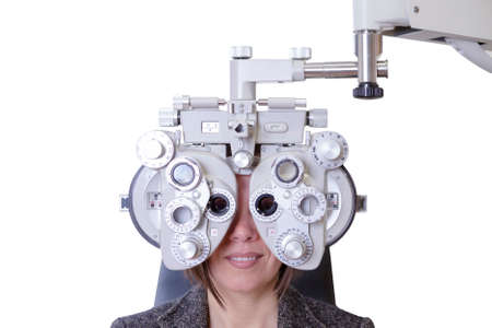 diopter: closeup of eyesight measurement to a young woman with a optical phoropter - focus on the phoropter center