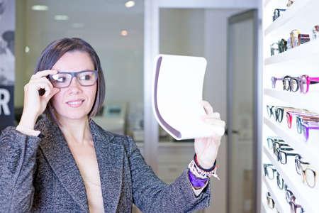 expositor: mujer joven que mira en un espejo pequeño está tratando de gafas junto a un expositor gafas en la tienda de óptica - se centran en el ojo derecho