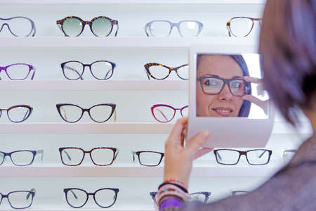 image of a smiling young woman reflected in a small mirror trying on glasses with a glasses exhibitor on background at optical store - focus on left eye Stock Photo
