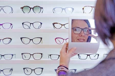 expositor: imagen de una mujer joven y sonriente se refleja en un espejo peque�o que intenta en gafas con un expositor gafas en el fondo en la tienda de �ptica - se centran en el ojo izquierdo