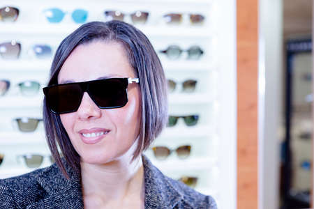 portrait of a smiling young woman at optical shop wearing very fashionable sunglasses with the sunglasses expositor at background - focus on the glasses center photo