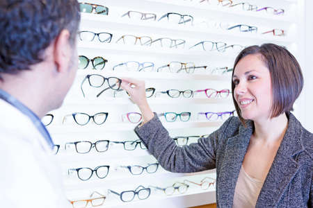 smiling young woman asking for advice to the optician and choosing glasses at the optical store - focus on the woman eyes photo