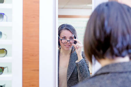 mirror image: mirror image of a smiling young woman trying on glasses in optical shop - focus on the woman left eye