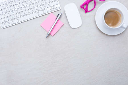 zenithal view of a business desk consisting on a a cup of coffee with a coffee saucer, wireless mouse, a keyboard, a pink eyeglasses and a pink sticky note with a pen on a beige desk background - suitable for copy space Stock Photo
