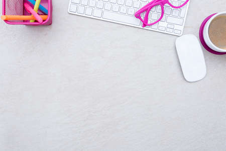 zenithal view of a business desk consisting on a white keyboard, a cup of coffee, a wireless mouse, a pink eyeglasses and colored markers on a beige desk background - suitable for copy space
