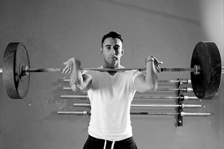jerk: male athlete is lifting a barbell at the crossfit box - focus on the man Stock Photo