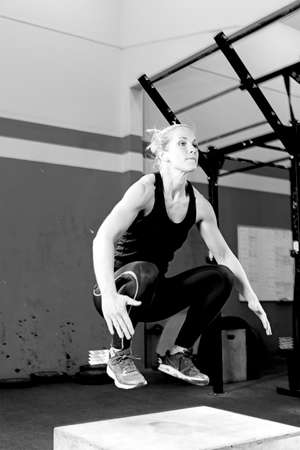 young female athlete doing a box jump at the box crossfit - focus on the woman Standard-Bild