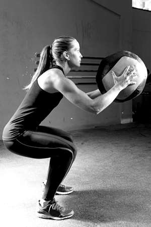 ball: profile of a young female athlete crouched doing wall balls exercises at the box crossfit - focus on the woman