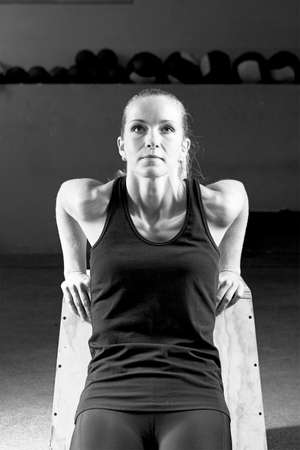 tricep: young female athlete making tricep pushups leaning on a wooden bench in the box crossfit - focus on the woman Stock Photo