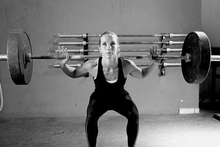 female athlete is lifting a barbell at the crossfit box - focus on the woman photo