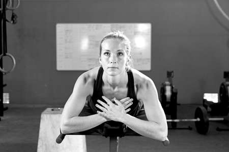 crunch: young female athlete with her arms crossed making glute ham raise exercise in the abdominal crunch machine at the box crossfit - focus on the woman