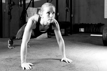 sport training: young female athlete is making push-ups at the crossfit box - focus on the woman
