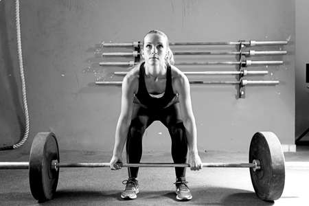 women body: female athlete is preparing to lift deadlift at the crossfit box - focus on the woman Stock Photo