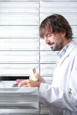 medicaments: smiling young male pharmacist taking a box of medicaments from a drawer - focus on the box Stock Photo