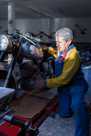 motorcycle repair shop: middle aged man placing a classic motorbike into the work platform at his workshop ready to start to restore - focus on the man