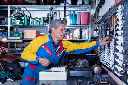 motorcycle repair shop: middle aged mechanic is taking a tool from a metal board at his workshop - focus on the man face
