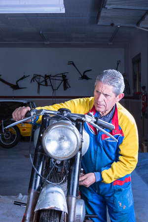 motorcycle repair shop: middle aged mechanic is starting a classic motorcycle checking the good functioning in process of restoration at his workshop - focus on the man face Stock Photo