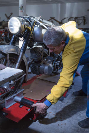 motorcycle repair shop: middle aged man adjusting a classic motorcycle into the work platform at his workshop ready to start to restore - focus on the man