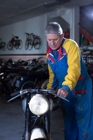motorcycle repair shop: middle aged man placing a classic motorcycle in the workshop ready to start to restore - focus on the man