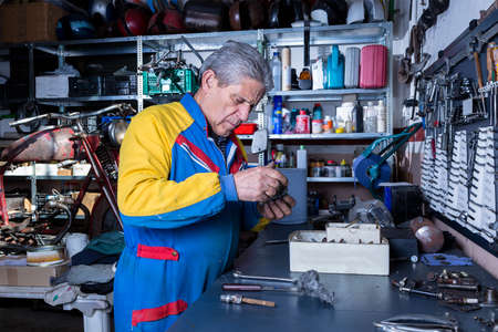 motorcycle repair shop: middle aged mechanic is cleaning a motorbike spare part with a metal scourer at his workshop - focus on the man face