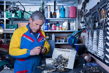 motorcycle repair shop: middle aged mechanic is looking for a spare part at his workshop - focus on the man face