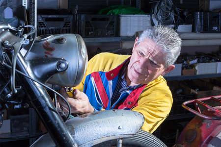 motorcycle repair shop: middle aged motorcycle mechanic is fixing the front headlight of a classic motorbike in process of restoration at his workshop - focus on the man face Stock Photo