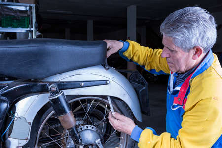 motorcycle repair shop: middle aged mechanic is adjusting the seat of a classic motorcycle in process of restoration at his workshop - focus on the man face Stock Photo