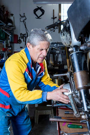 motorcycle repair shop: a middle aged mechanic is repairing the engine of a classic motorcycle in process of restoration at his workshop - focus on the man face Stock Photo