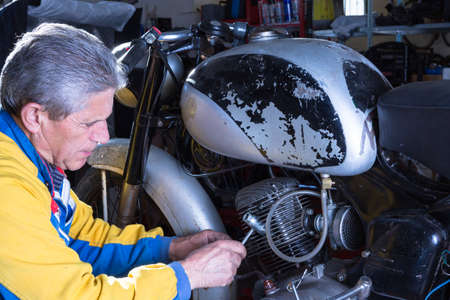 motorcycle repair shop: a middle aged mechanic is repairing the engine of a classic motorbike in process of restoration at his workshop - focus on the man face Stock Photo