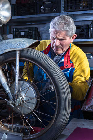 motorcycle repair shop: middle aged mechanic sanding the wheel spokes of a classic motorbike with a metal scourer in process of restoration at his workshop - focus on the man face