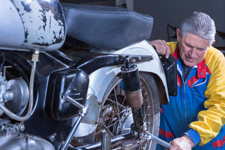 tightening: middle aged mechanic is tightening the shock absorber of a classic motorcycle with a wrench in process of restoration at his workshop - focus on the man face