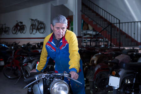 motorcycle repair shop: middle aged man placing a classic motorcycle at his workshop ready to start to restore - focus on the man Stock Photo