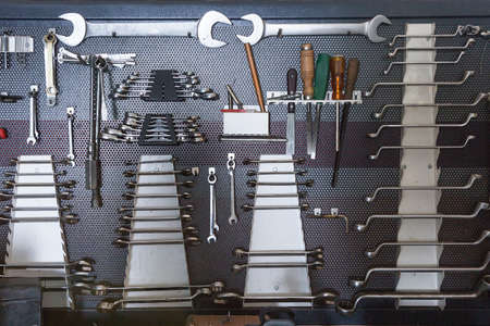 mechanic tools hanging on a organized board on a vehicle reparation workshop Standard-Bild