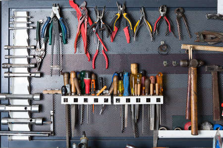 mechanic tools hanging on a organized metal board at a vehicle reparation workshop