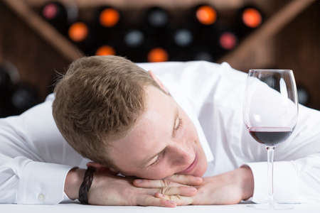 comical: comical photo of a smilling young man at the end of a wine tasting session with a red glass of wine - focus on the man face