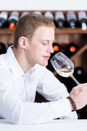 olfactory: young man on a wine tasting session on the olfactory phase is analyzing the white wine smelling the wineglass at a restaurant - focus on the man face