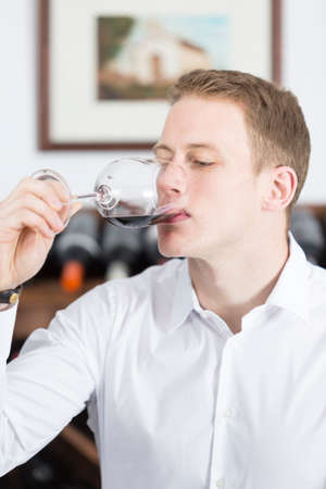 gustatory: young man on a wine tasting session on the gustatory phase is tasting the red wine at a restaurant - focus on the man face