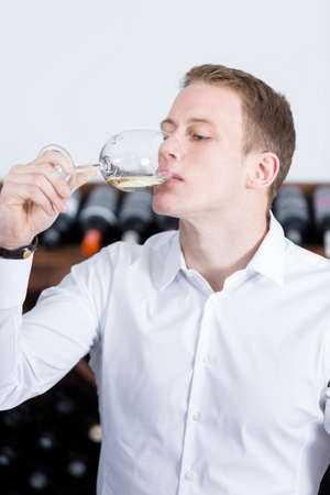 gustatory: young man on a wine tasting session on the gustatory phase is tasting the white wine at a restaurant - focus on the man face