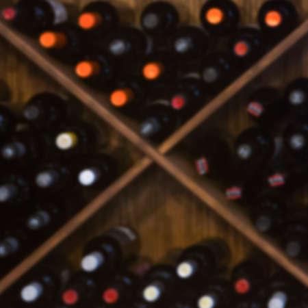 exhibidor: botellero de madera fuera de foco con botellas de vino tinto - �til como fondo Foto de archivo