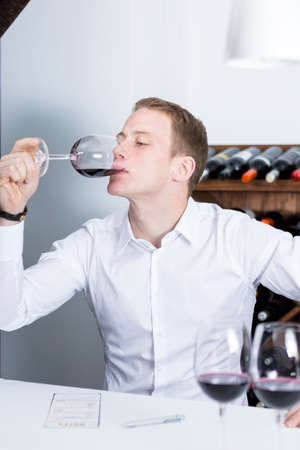 gustatory: young man on a wine tasting session on the gustatory phase tasting the red wine is writing down in a wine tasting sheet at a restaurant male winemaker smelling a red wineglass - focus on the man face