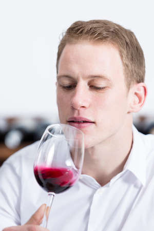 olfactory: man on a wine tasting session on the olfactory phase is analyzing the red wine shaking the glass of wine at a restaurant - focus on the man face