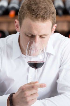 olfactory: young man on a wine tasting session on the olfactory phase is analyzing the wine with the wineglass in the nose at a restaurant - focus on the man face Stock Photo
