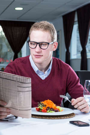 financial newspaper: young businessman eating a salad while is reading a financial newspaper on a working lunch at a restaurant - focus on the man face Stock Photo