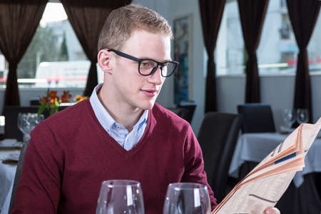 financial newspaper: young businessman is reading a financial newspaper while he waits for a meal at a restaurant - focus on the man face