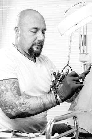 male tattooer is tattooing the back of a young woman in the tattoo cabin at his tattoo shop - focus on the man face Stock Photo