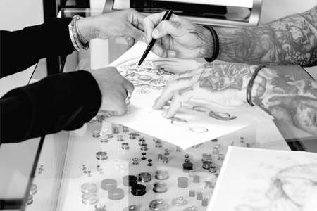 tattoo: detail of a tattoo design of a tattoo artist is showing to a young female customer the tattoo design before the tattoo session at the tattoo shop - focus on the tip of the pen